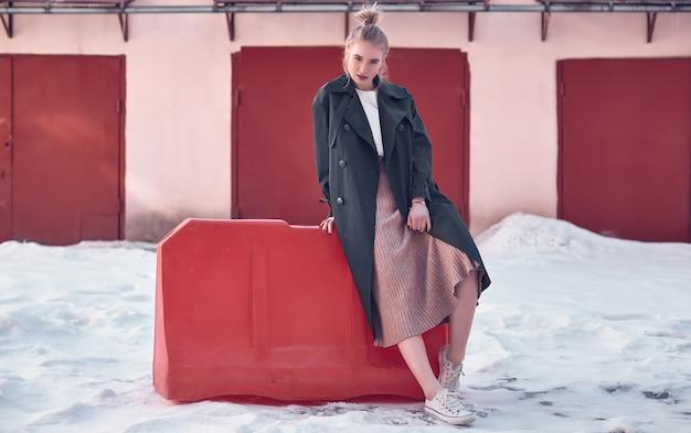 Hermosa mujer rubia hipster vistiendo moda abrigo largo y vestido en la calle