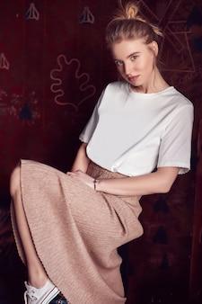 Hermosa mujer rubia inconformista en camiseta blanca y vestido sentado en el sofá