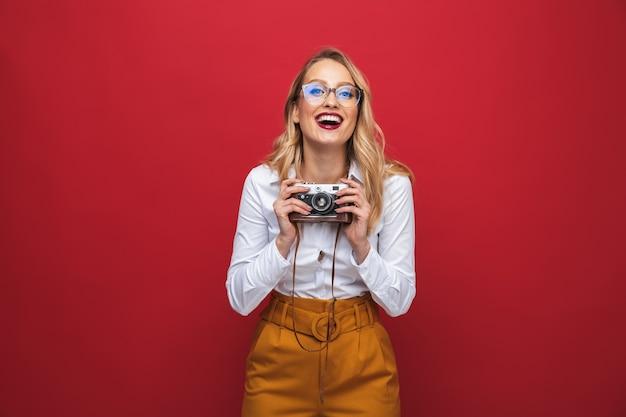 Hermosa mujer rubia joven feliz que se encuentran aisladas sobre fondo rojo, sosteniendo la cámara de fotos