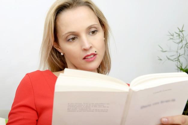 Hermosa mujer rubia lee un libro en el sofá