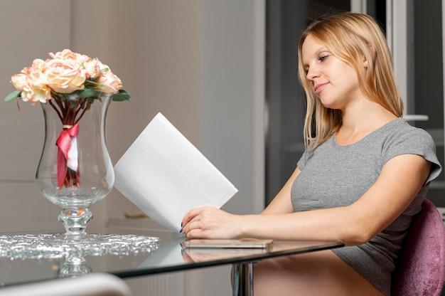 Hermosa mujer rubia leyendo en la mesa