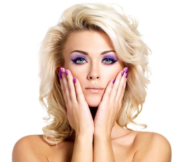 Hermosa mujer rubia con manicura belleza púrpura y maquillaje de ojos. modelo de moda con peinado rizado.