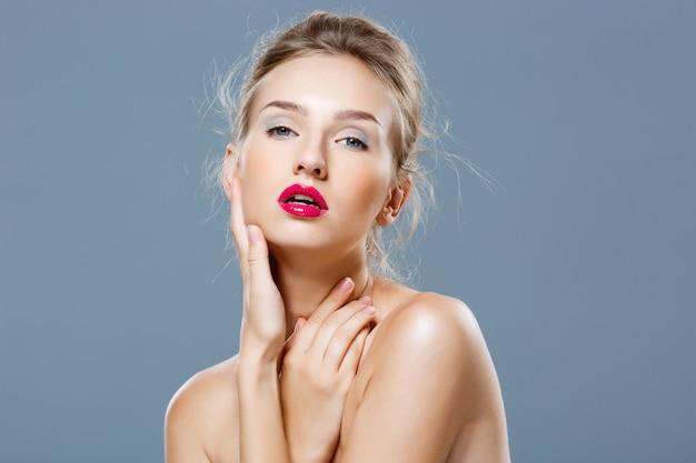 Hermosa mujer rubia con maquillaje brillante posando