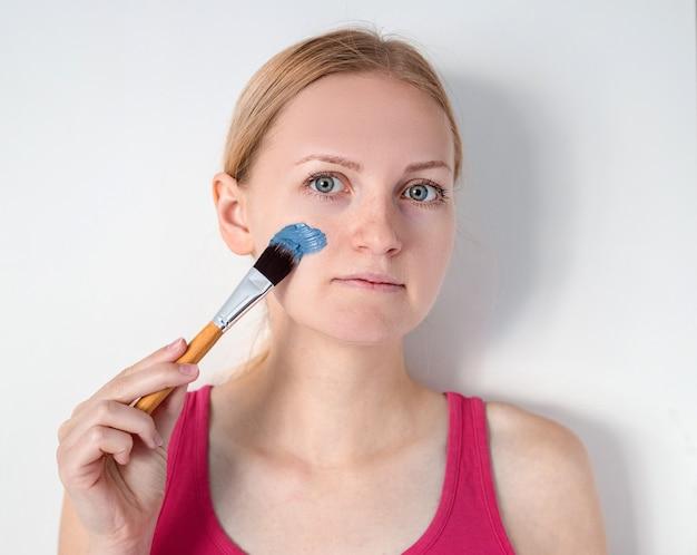 Hermosa mujer rubia con máscara facial de arcilla azul aplicar por esteticista. mujer con una máscara en una mejilla está sonriendo