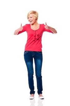 Hermosa mujer rubia mostrando los pulgares para arriba
