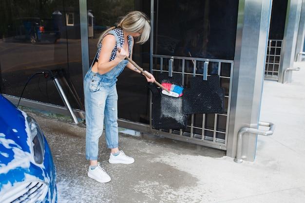 Hermosa mujer rubia en overol de mezclilla lava el coche