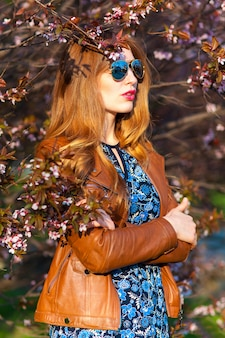 Hermosa mujer rubia en el parque en un cálido día de primavera