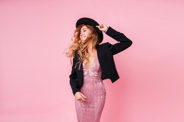 Hermosa mujer rubia con peinado ondulado perfecto en vestido de fiesta de lentejuelas rosa posando en la pared de color rosa pastel. publicidad, salón de belleza, boutique de moda.
