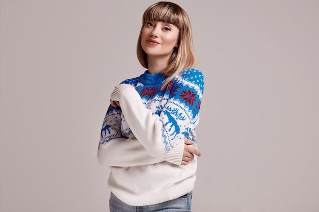 Hermosa mujer rubia con pelo corto en suéter de navidad