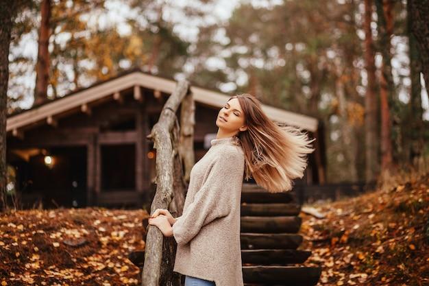Hermosa mujer rubia de pie cerca de la escalera de madera