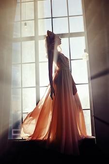 Hermosa mujer rubia de pie en la ventana de la luz del sol
