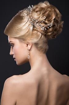 Hermosa mujer rubia con piel perfecta, maquillaje de noche, peinado de novia y accesorios