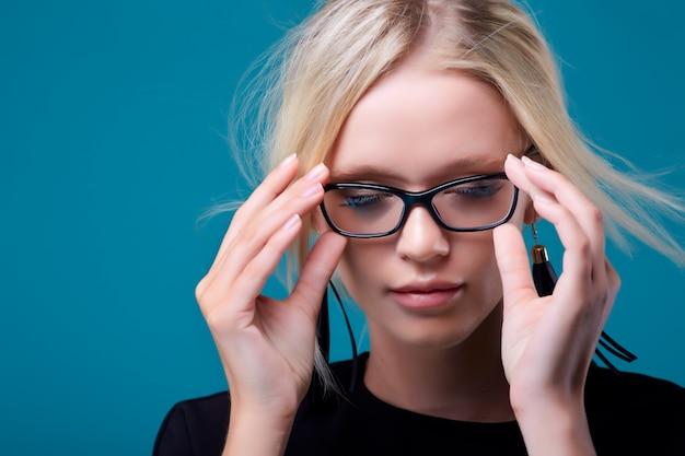 Hermosa mujer rubia piensa con gafas
