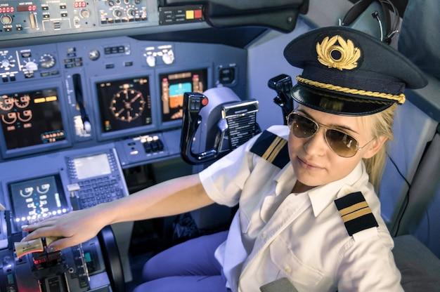 Hermosa mujer rubia piloto vistiendo uniforme y sombrero con alas doradas
