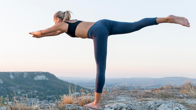 Hermosa mujer rubia practicando yoga al aire libre