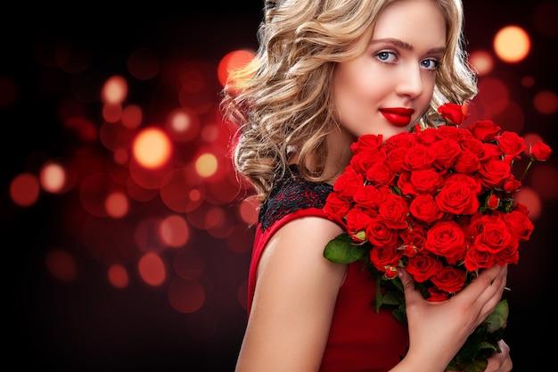 Hermosa mujer rubia con ramo de rosas rojas