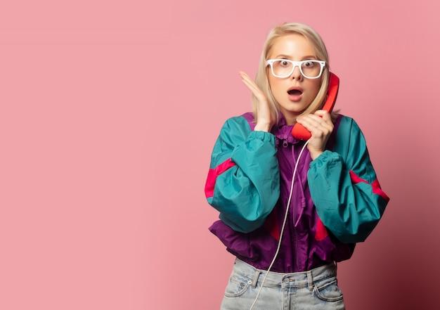 Hermosa mujer rubia en ropa de los años 90 con auriculares