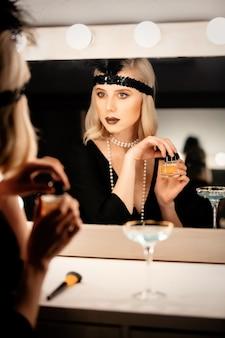 Hermosa mujer rubia en ropa de veinte años aplicando maquillaje cerca de un espejo con bombillas