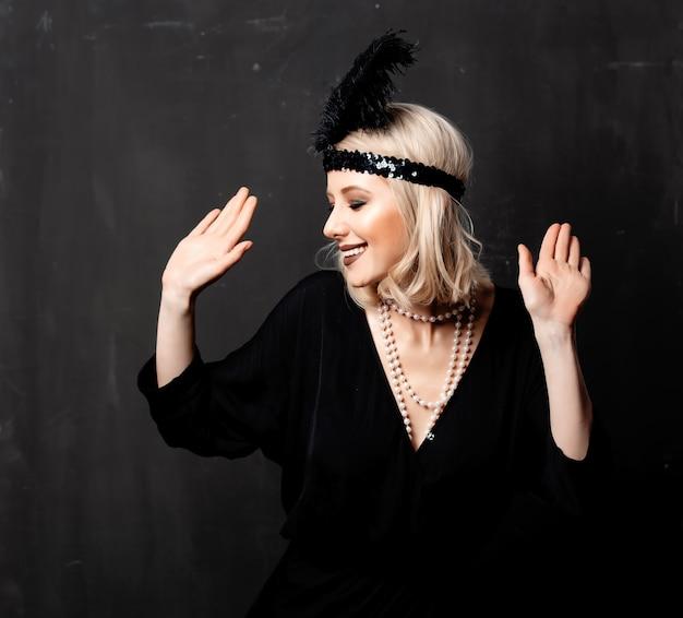 Hermosa mujer rubia en ropa de veinte años bailando sobre fondo oscuro