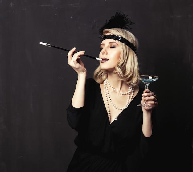 Hermosa mujer rubia en ropa de veinte años con pipa y cóctel sobre fondo oscuro