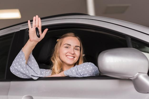 Hermosa mujer rubia saludando desde un auto
