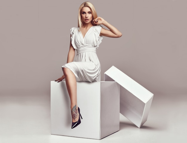 Hermosa mujer rubia sensual en vestido blanco en una gran caja de compras
