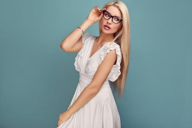 Hermosa mujer rubia sensual en vestido blanco de moda