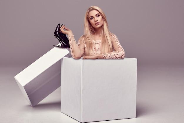Hermosa mujer rubia sensual en vestido rosa posando en una gran caja de compras