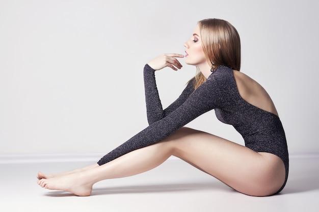 Hermosa mujer rubia sexy. niña sentada en el piso