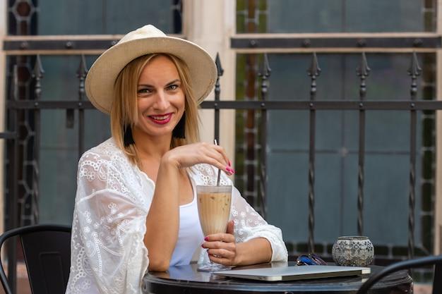 Hermosa mujer rubia con sombrero para el sol vestida con ropa ligera sentado en un café al aire libre y bebiendo un cóctel.