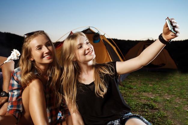 Hermosa mujer rubia sonriendo, haciendo selfie camping parrilla malvavisco.