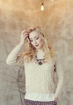 Hermosa mujer rubia en suéter beige