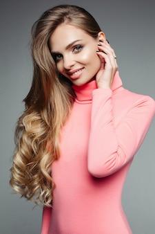 Hermosa mujer rubia en suéter rosa con cabello ondulado y voluminoso.