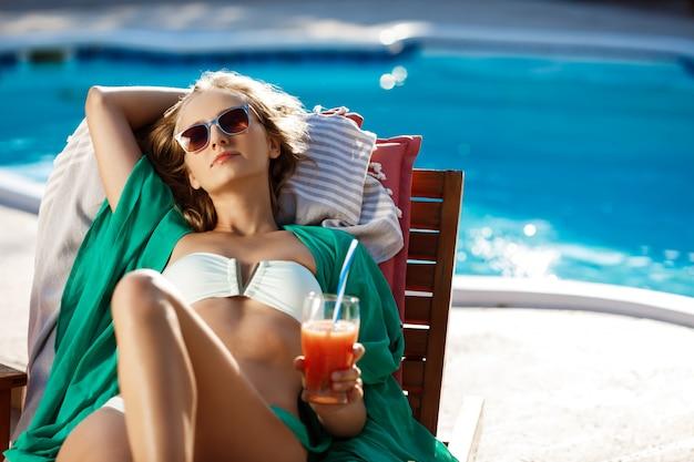 Hermosa mujer rubia tomando el sol, bebiendo cócteles, tumbado junto a la piscina