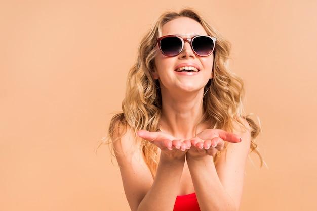 Hermosa mujer rubia en top rojo y gafas de sol con las palmas hacia arriba