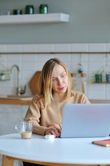 Hermosa mujer rubia trabajando con su computadora portátil mientras está sentado en la cocina de su apartamento