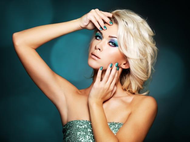Hermosa mujer rubia con uñas verdes y maquillaje glamour de ojos