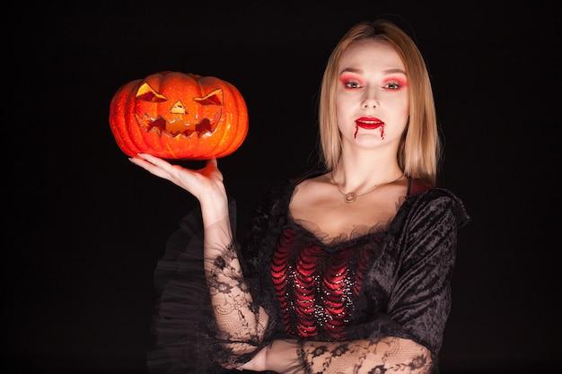 Hermosa mujer rubia vestida como un vampiro malvado sosteniendo una calabaza para halloween.