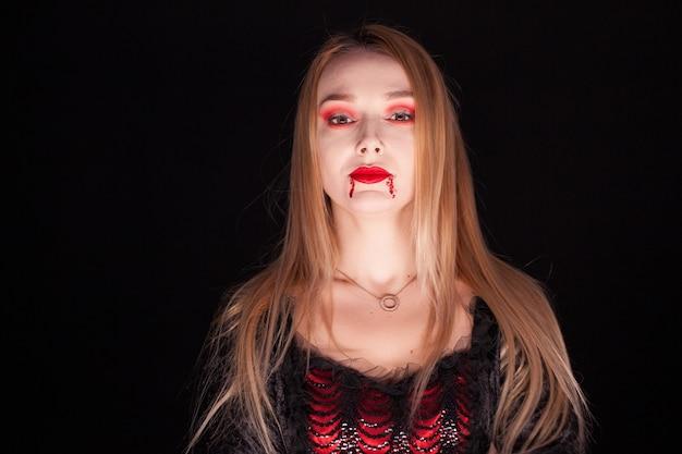 Hermosa mujer rubia vestida como un vampiro sobre fondo negro.