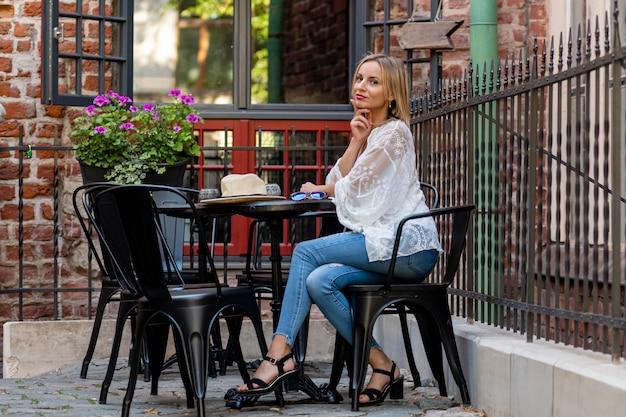 Hermosa mujer rubia vestida con ropa ligera sentada en un café al aire libre y bebiendo un cóctel