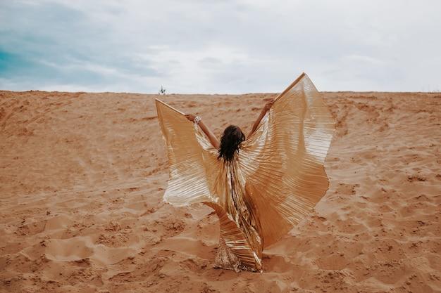 Una hermosa mujer rubia en un vestido dorado con brillantes con alas, el traje está bailando una danza oriental, oriental en el desierto en la arena. hermosa mujer exótica bailarina en un traje para la danza del vientre.