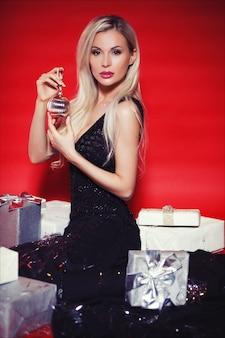 Hermosa mujer rubia en vestido largo negro con cajas de regalo y confeti cayendo sobre el fondo rojo aislado