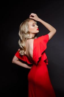 Hermosa mujer rubia en vestido de noche rojo