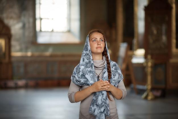 Hermosa mujer rusa caucásica con cabello rojo y un pañuelo en la cabeza está en la iglesia ortodoxa, enciende una vela y reza frente al icono.