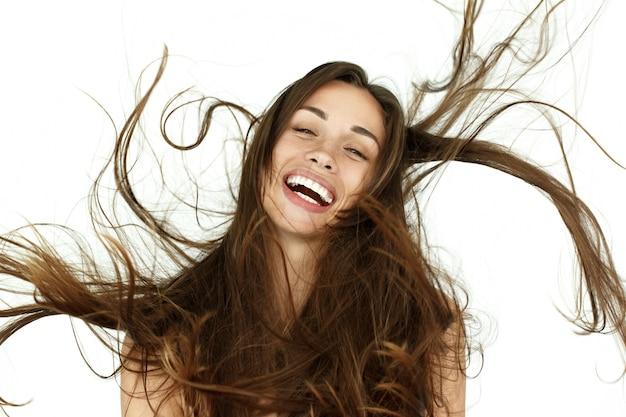 Hermosa mujer sacude su cabello sobre fondo blanco
