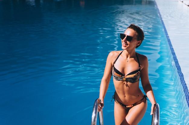 Hermosa mujer saliendo de la piscina