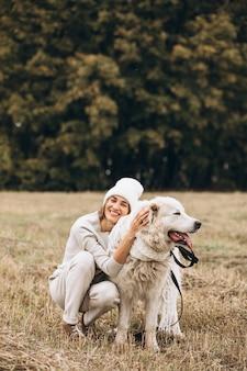 Hermosa mujer saliendo de su perro en un campo