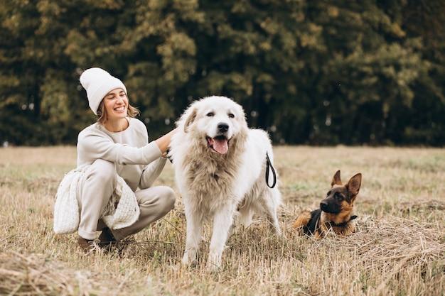 Hermosa mujer saliendo de sus perros en un campo