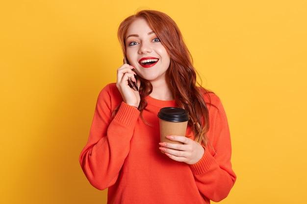 Hermosa mujer satisfecha con mirada emocionada, disfruta de café para llevar caliente