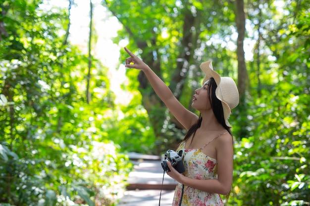 Hermosa mujer señalando con el dedo a algo en el cielo en el jardín